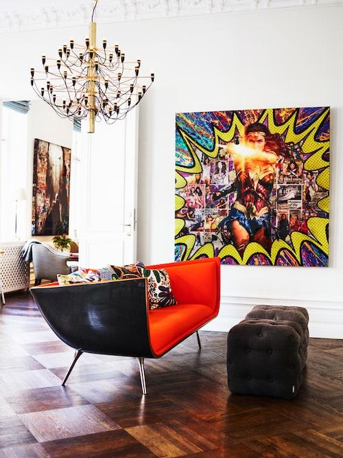"""Ett riktigt sprakande vardagsrum hemma hos Johan och frun Paulina. """"Raggarbilssoffan"""" Shaipa är gjord av Johans kompis Felix Bonnier. Taklampa Sarfatti, Flos. Paulina älskar superhjältar och tavlan på henne som Wonder woman är gjord av New York-konstnären De-Von."""