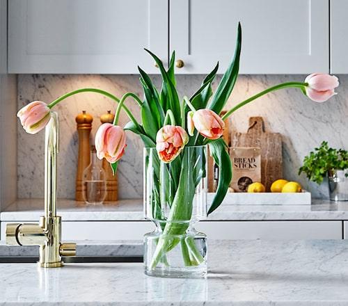 Färgklickar som lyser i det grå: mässingsblandare och tulpaner.
