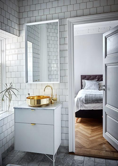 Guldstänk i det avskalat vita. Toalettskåp med marmorskiva, design av Superfront på Ikeas stomme Bestå. Blandare, Tapwell, och handfat från Superfront. Sovrummet är ombonat i varm gråskala. Säng från Carpe diem, kuddar, Wallboe interior.