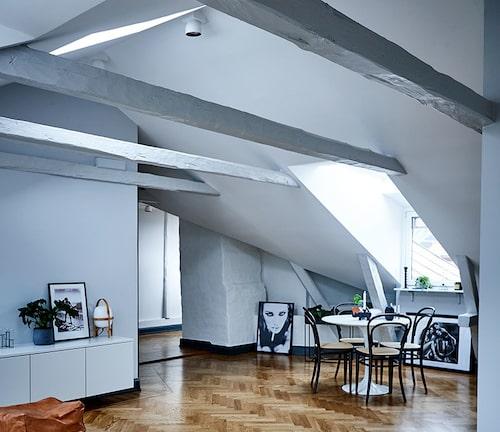 """Designklassiker och fotokonst under takåsarnaVindsliv med synliga takbjälkar. Med den enbenta kollektionen Tulip avlägsnade Eero Saarinen den """"fula, förvirrade och inte rogivande"""" världen under stolar och bord, för Knoll 1957. Michel Thonets böjträklassiker No 14, från 1859, är världens genom tiderna mest sålda stol. Fotografierna, köpta på nätet, står lika bra lutade när väggar saknas."""