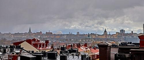 De röda och svarta plåttaken hör Stockholm till. Liksom kyrktornen som här reser sig vid horisonten. Till vänster om Globen syns Sofia, till höger Katarina kyrka.
