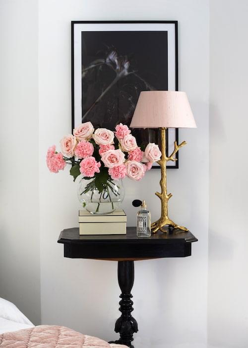 Snittblommorna tar upp färgen i överkast och lampskärm. Det antika pelarbordet är inropat på auktion och ommålat i svart högblank snickerifärg. Lampfoten i mässing från Oscar&Clothilde.
