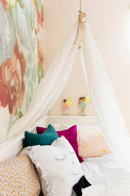 På en rundstav fäst med rep på krokar i taket hänger ett skirt linnetyg över sängen. Mysigt att sova under! Kuddarna är både köpta och hemsydda, ansiktet på en av dem ritades med textilpenna.