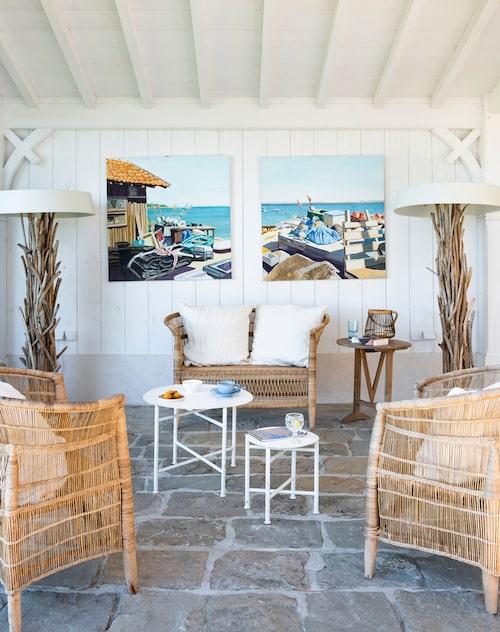 Sitthörnan i ljusa pasteller och naturmaterial tar upp husets färger. Rottingmöbler från As'art. Golvlampor, Bleu nature, små bord, Cinq-étoiles, målningar av Andrée Léger.