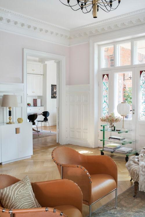"""Även vardagsrummet har utgång mot terrassen. De vackra målningarna på glasdörrarna är original. """"Man kan se när solen ligger på att de är lite blekta."""" Skinnfåtöljer Bruno av Mats Theselius för Källemo."""