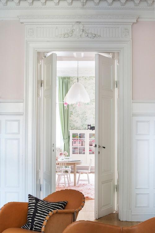 Genom dubbeldörrarna med rikt dekorerade överstycken ser man in till döttrarnas rum från vardagsrummet. Tyllampan matchar barnens balettintresse.