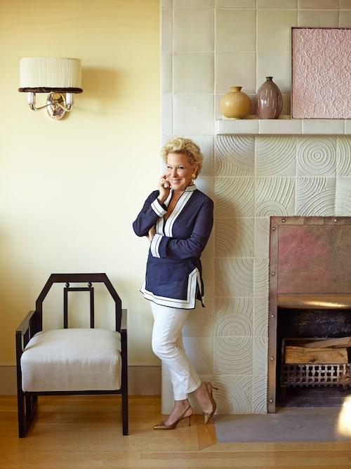 Bette Midler framför den öppna spisens handgjorda mönstrade kakelplattor.