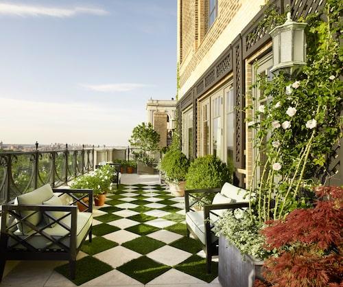Man undrar om terrassen sköts om med hjälp av nagelsax och handdammsugare… Kalkstensplattor och gräsrutor bildar mönster på terrassen utanför vardagsrummet.