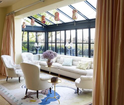 """Familjen älskar sitt """"sunroom"""", den inglasade alkoven i vardagsrummet där de brukar sitta och dricka kaffe och läsa tidningen. Lamporna i taket är gjorda av kimonor."""