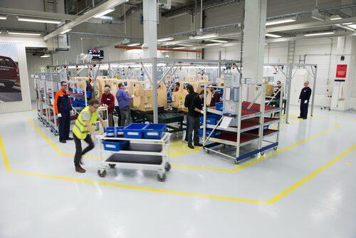 """Glenn """"Trucken"""" Lindberg i gul säkerhetsväst levererar material till Teknikens Världs bilbyggare."""