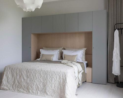 Tryggt och samtida. Sängen är förankrad under, och mellan skåpen, med släta luckor, i milt grått och trärent vid huvudgärden. En snygg och yteffektiv förvaringslösning ur serien Contemporary från Kvänum, men du kan göra en egen budgetvariant med skåp från exempelvis Ikea.