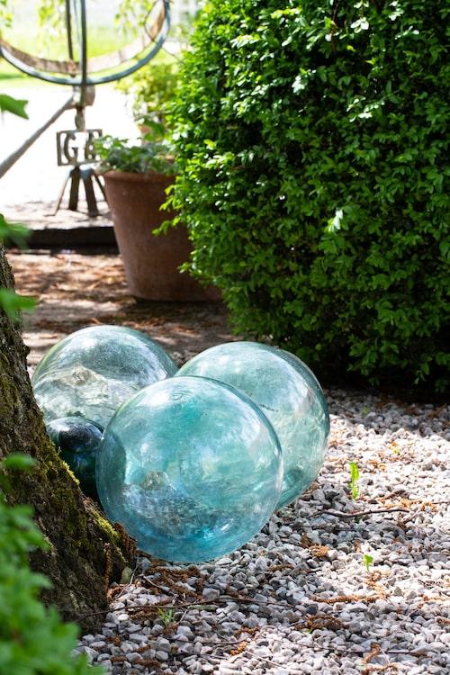 De stora glaskloten som utgör blickfång under gårdsplanens björk, är gamla flytbojar utan nät.
