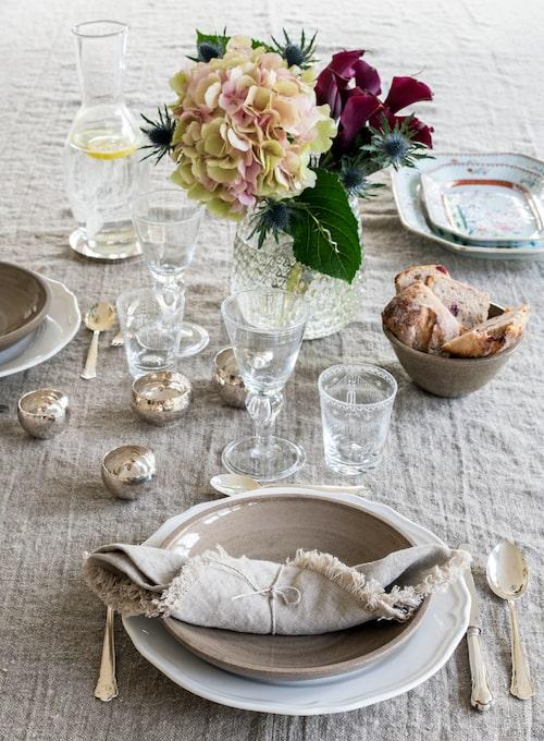 Den grova, oblekta linneduken kunde lika gärna ha varit fransk, men den här kommer från Axlings linne. Keramiktallrikar från Mölle krukmakeri, glas från Reijmyre glasbruk och Vas Vitreum, silverskålar av Rey Urban.
