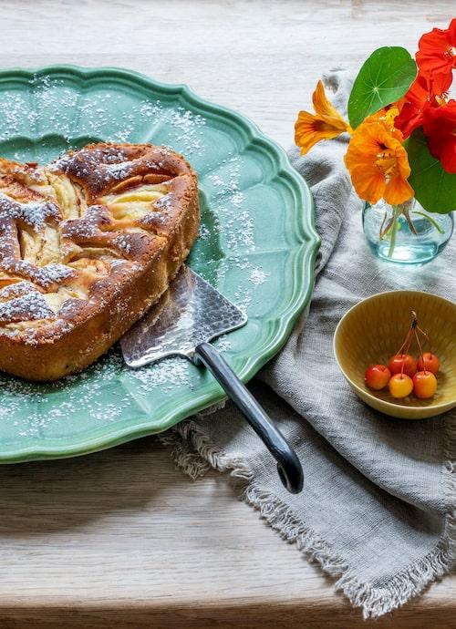 Äppelträd i trädgården förpliktigar: Nybakad äppelkaka efter Sånga-Säbys recept, serverad  på grönt 40-talsfat.