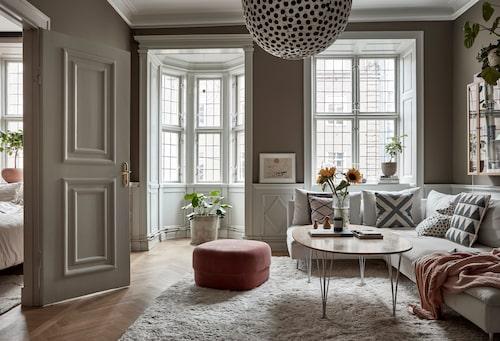 Vardagsrummets burspråk och paneler tillkom i början av 1900-talet då huset renoverades i historiserande stil. Den fluffiga mattan är från Layered och puffen från Normann Copen-hagen. Soffa, Ikea och soffbord av Arne Jacobsen. Prickig taklampa från Afroart.