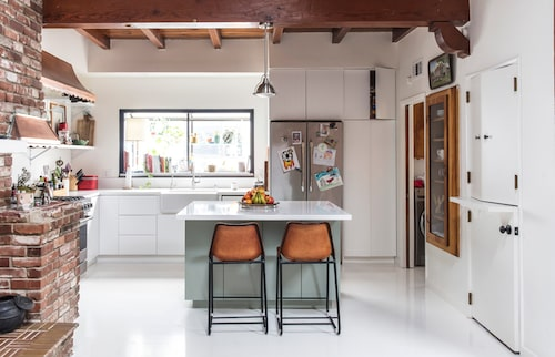En murad öppen spis ger karaktär åt huset. Stolar vid köksön från C8. Till höger syns det inbyggda vitrinskåpet.