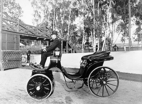 Detta är ingenjör Harald Håkansson från Eslöv. Han jobbade i Berlin och lärde sig mycket om elbilar. Han återvände till Sverige och 1898 började han bygga en egen elbil. Drivpaketet sitter under Håkansson. Journalister tyckte att den var bullrig.