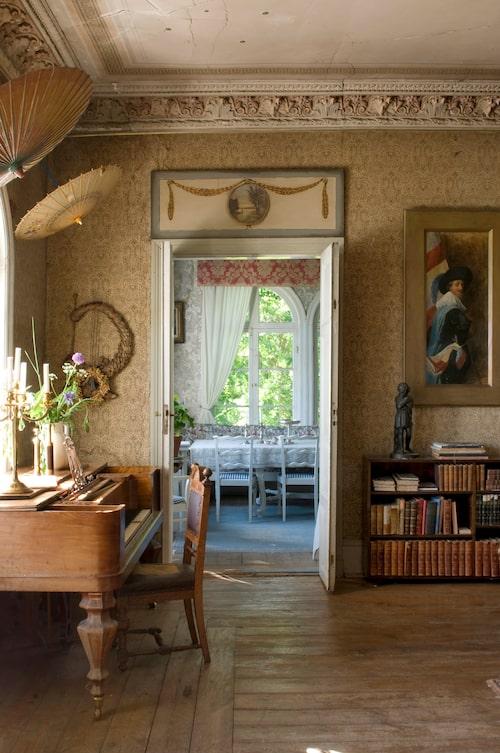 Vy mot lilla matsalen på västra gaveln. Överstycket till dubbeldörren är dekorerat med motiv från de fyra årstiderna. Taffeln är husets andra exemplar och secondhandfyndad av Bosse. På väggarna kinesiska parasoller för att dämpa ljudet.