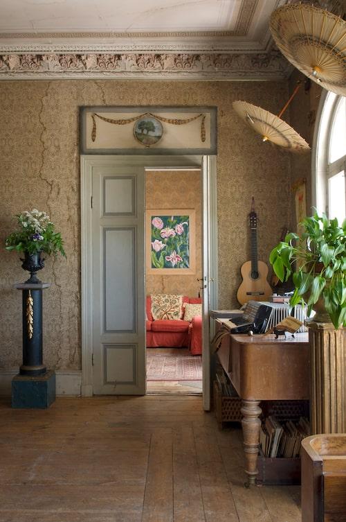 """""""Vi har försökt gnida rent stuckaturen med limpor, men lite sot gör inget. Tapeten tror vi är original eller från den stora renoveringen år 1900, fuktfläckarna är kvar från tiden när det regnade rakt in. Hela innertaket hängde när vi kom hit 1981. Taffeln fanns i huset men behövde renoveras. Blomstertavlan i rummet intill, har Lotten målat."""""""