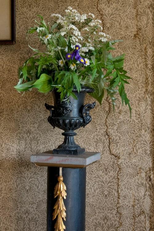 """""""Lotten älskar att arrangera blommor, det är hennes terapeutiska stund. Gjutjärnsurnan är gammal men piedestalen är gjord av ett cementrör och dekorerad med bladguld, den fanns i huset när vi kom."""""""