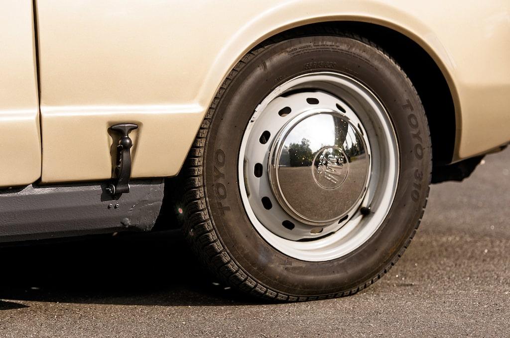 Klassiska gummistroppar låser det uppfällbara huvpartiet framtill. Femton tum höga fälgar på en så liten bil från 1960-talet – ovanligt.