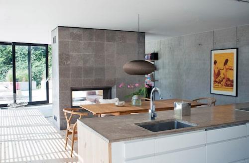 """Kök och vardagsrum åtskiljs av brasväggen, klädd med kalksten. Den öppna planlösningen och de """"enkla"""" materialen leder tankarna till de så kallade case study houses man lät bygga på 50- och 60-talen i Kalifornien. Eftersom rummet flödar av ljus fungerar det fint med de mörkare råa materialen. Köket är från Ballingslöv, bänkskivan är betong. På väggen ett konstverk av Tracey Nakayama."""