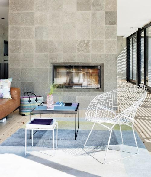Vardagsrumsdelen skiljs från köket av den kalkstensklädda skiljeväggen, där glaset gör att man kan se brasan från båda håll. Matta och soffbord från Hay. Harry Bertoias Diamond chair ritad 1952, förstärker Mid-century modernkänslan i huset. Vasen av Heath ceramics i Kalifornien