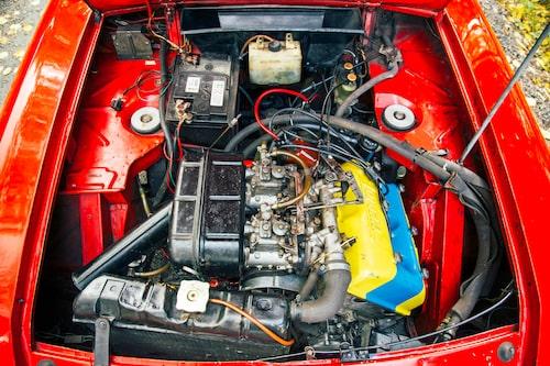 """V4-motorn lutar 45 grader i Fulvia. Ventilkåpan är gul på alla HF-versioner. Version """"1016"""" med 132 hästkrafter har ett blått band över kåpan."""