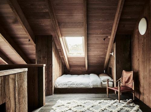 Gästrummet är lika enkelt som vackert inrett. Marockansk matta och vintagestol i safarimodell.