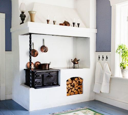 """Järnspisen kommer från originalhuset liksom golvbräderna. Men eldstaden murade de upp själva. """"Vasen på spisel-kransen har Joakims mamma, keramikern Greta Lundström, gjort. Vi har många av hennes alster i huset."""""""
