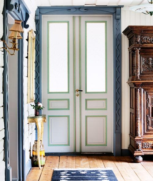 """Pardörrarna i hallen är köpta begagnade, men fodren är hemfrästa efter eget mönster. """"Vågmönstret kom till då vi provade oss fram med bandsåg för att se hur snirkliga vi kunde göra mönstren."""" Skåpet är ett auktionsfynd, hallbordet och spegeln är från loppis. På golvet röllakansmatta. """"Golvbräderna från originalhuset räckte bara till hallen och köket."""""""