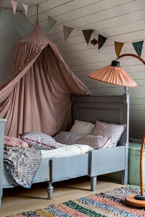 Dottern Indies antika växasäng i duvblå färg passar fint ihop med den rosa sänghimlen från Numero 74 och golvlampan från 30-talet. Småmönstrade kuddar från Bungalow.