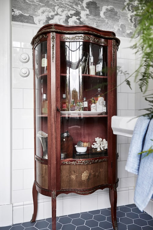På sirliga ben. Ett antikt vitrinskåp, inköpt på auktion, blev ett badrums- skåp och ett kul ögongodis. Strömbrytare från Byggnadsvårdsbutiken.