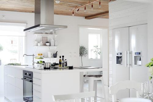 Plankväggen bygger in vitvarorna för lantlig feeling.