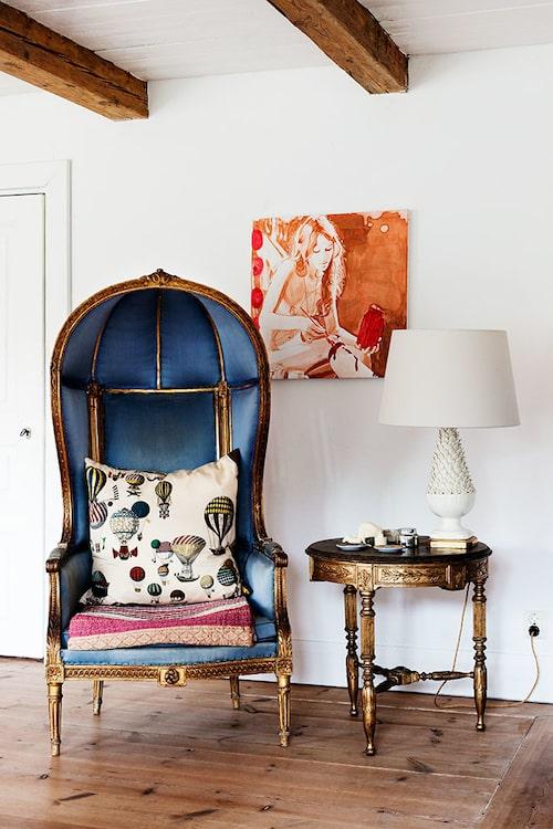 """I vardagsrummet står en bergère i Louis seize stil. Stolen blir alltid en """"conversation piece"""" – alla älskar den, men den är inte så bekväm att sitta i. Kudde i Fornasettityg. Bordet är ett hobbyarbete av en Mörner från början av 1800 talet. Målning av Tracy Nakayama."""