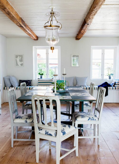 Kökets matplats med antikt slagbord i grön originalfärg och sengustavianska stolar. Den platsbyggda sittbänken rymmer stora lådor för förvaring. Ljusampeln är en nygjord variant av äldre original framtagen av Lars Sjöberg. Alla golvtiljor i huset är nya. På väggen teckningar av Maria Finn.