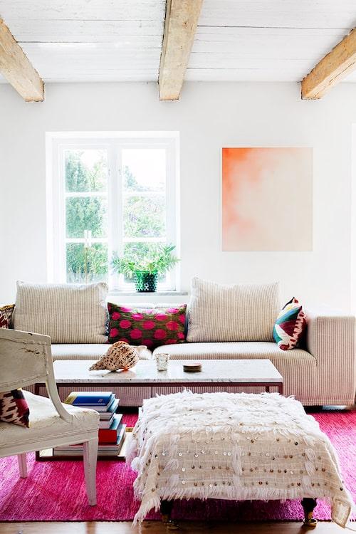 Vardagsrummets lite mer moderna attityd kontrasterar mot den antika inredningen i övriga rum. Soffa från Eilersen, soffbord av Ulf Scherlin och pläd från Turkiet. Karmstol från 1800 talet, målning av Derek Root, matta, Vandra rugs.