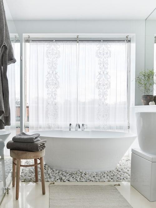 Som insynsskydd har det stora fönstret en skir gardin som silar ljuset, från Zara home. I nedsänkningen framför fönstret står badkaret på en bädd av vita stenar. Träpall, Love warriors, och gråbeige frottéhanddukar och morgonrock, allt från Axlings linne, som bryter fint mot allt det vita. MattaHerringbone, Classic collection. Terrakottabrun lerkruka, Love warriors, växt, Magnolia i Sjöstaden.