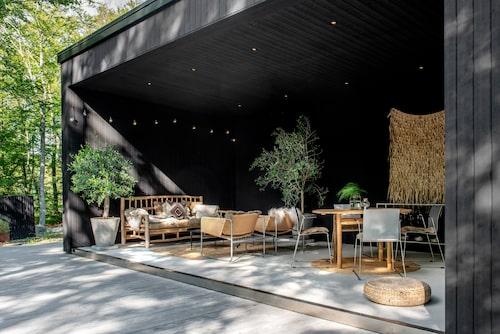Uterummet erbjuder skyddat läge från vindar och sol. Soffan är från Ilva, fåtöljerna, Ikea. Runt matbord i obehandlad teak, Housedoctor, stolar från Blå station i Åhus. Vassbonaden på väggen är från Madam Stoltz.