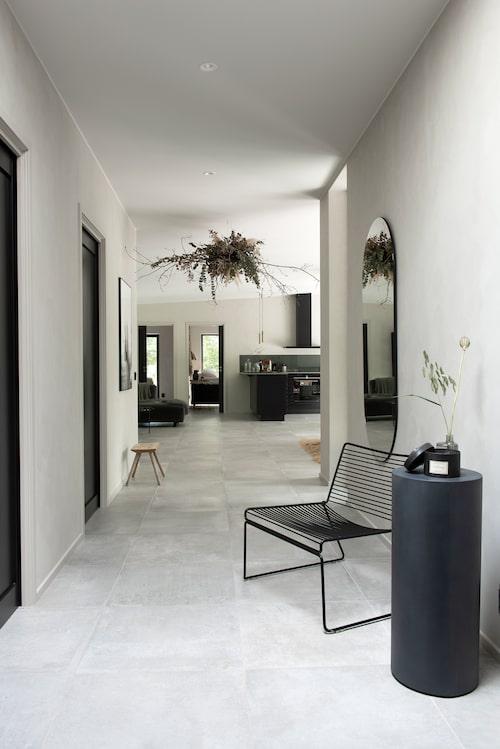 I entréhallen står en piedestal i metall, Tine K home. Stol från Hay och ellipsformad spegel, Housedoctor. Blomsterarrangemanget i taket är från Blond flores i Bromölla.