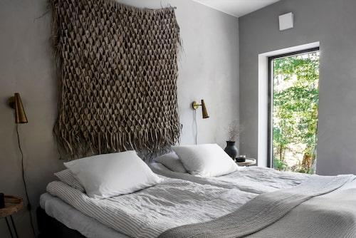 I parets sovrum står dubbelsängen Kontinental från Mio. Sänglampor Precis från Housedoctor och sängbord från Apotekarns på Svabeholms kungsgård. Vassdekoration, Madam Stoltz.