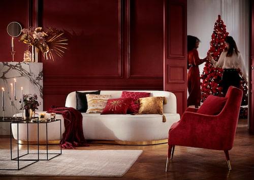Med ett par kuddar i grönt, rött och guld blir det julstämning i soffan.