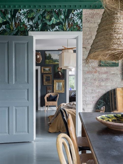 Blick från matrummet in i sovrummet. Tapeten till vänster är från Bauhaus, på väggen till höger har teglet frilagts. Taklampan inne i sovrummet följde med vid husköpet.