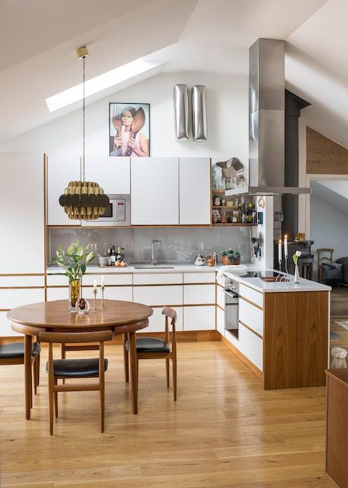 Fyra meter upp till nock och takfönster på det. Det blir etthärligt ljus i köket. När stolarna skjuts in under bordet bildar matgruppen en cirkel. Design Hans Olsen för Frem Röjle 1956.