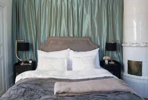 Sidentyget från Mimou döljer en dörr in till nästa rum och sattes upp för att det här var enda platsen i rummet där en dubbelsäng fick plats. Smart och vackert. Sänggavel i fuskmocka från Mimosa by Inka, sängkläder från Mimou, överkast från Day home, lt från Oscar & Clothilde.