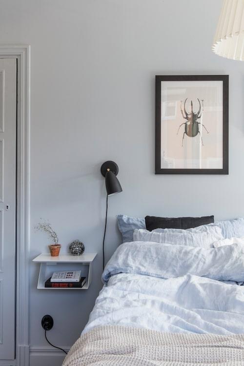Sovrummets väggar är målade rofyllt ljusblått. Hyllan bredvid sängen kommer från Designtorget. Sänglampa, Norrmalms el.