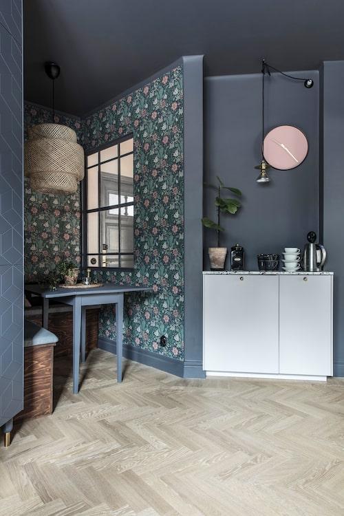 I kökets lilla matvrå har Lina och Viktor själva byggt en bänk. Fönstret gör att det inte känns instängt. William Morris-tapeten poppar fint mot väggar och tak som är målade i samma grå nyans.