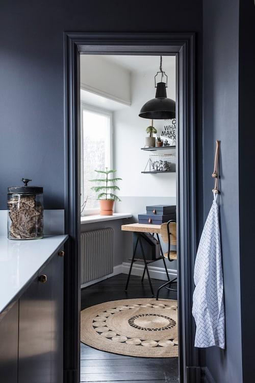 Från köket nås arbetsrummet som är inrett med bord och stol från Ikea. Taklampa och matta från Granit, hyllor från Designtorget.