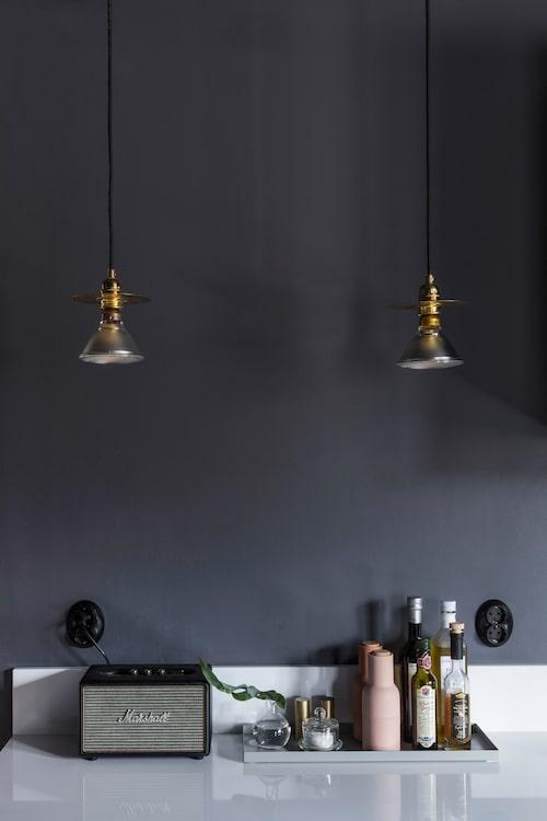 Bänkskivan i köket är av komposit och köpt hos Granitkungen. Lamporna från Norrmalms el tillför lite bling mot den mörka väggen.