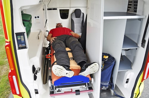 Patient Hedberg provar båren som enkelt skjuts in på gejderräls. Stående stuvfack på höger sida.